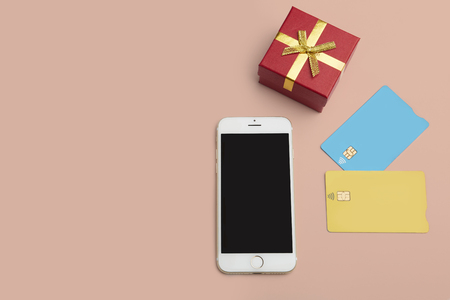 Mockup of two blank color credit cards, smartphone, gift box on empty desk. Business mock-up background for message writing.Top view. Horizontal
