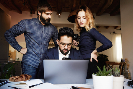 Group of three young coworkers discussing new ideas at modern studio using mobile laptop computer. Horizontal, blurred background.Blurred background