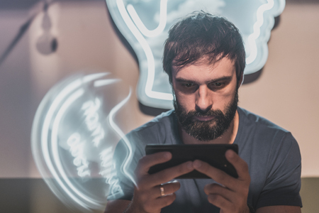 Portrait of Young bearded man sitting in cafe and holding hands mobile phone and typing screen. Horizontal. Blurred background. Visual effects. Color masks Stock Photo - 101151055