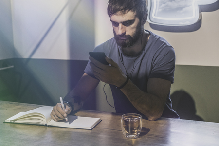 Young bearded man sitting in cafe and using mobile phone for listening digital music. Man making notes at note book. Horizontal. Blurred background