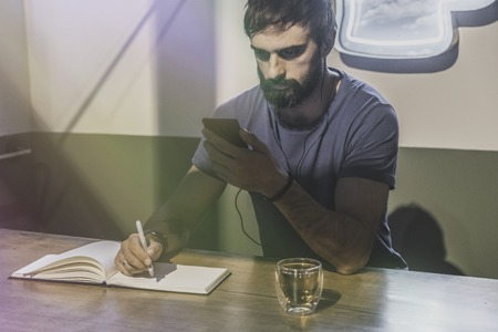 Young bearded man sitting in cafe with headphones. Men using mobile phone for listening digital music on smartphone. Man making notes at note book. Horizontal. Blurred background. Visual effects Stock Photo - 101151056