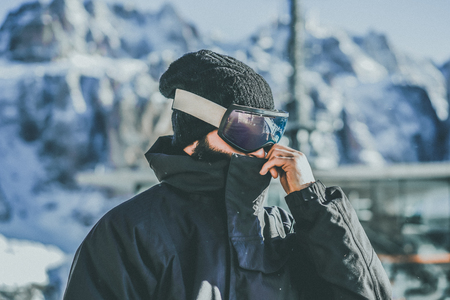 Portrait of bearded young snowboarded in sunglass mask, at the ski resort on the background of mountains and blue sky.Blurred background.Horizontal image. Stock Photo