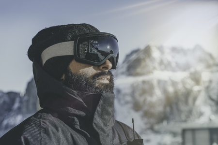 Close-up portrait of bearded young snowboarded in sunglass mask, at the ski resort on the background of mountains and blue sky.Blurred background.Horizontal. Visual and flare effects Stock Photo - 101272663