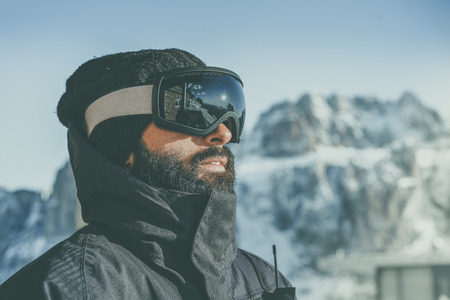 Close-up portrait of bearded young snowboarded in sunglass mask, at the ski resort on the background of mountains and blue sky.Blurred background.Horizontal. Colors effects