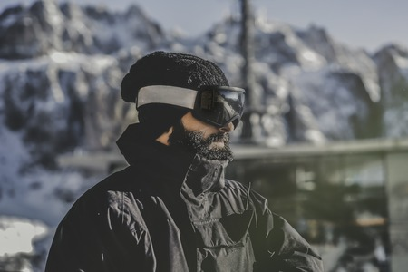 Close-up portrait of bearded handsome snowboarded in sunglass mask, at the ski resort on the background of mountains and blue sky.Blurred background.Horizontal. Stock Photo - 101138472