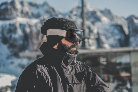 Portrait of bearded handsome snowboarded in sunglass mask, at the ski resort on the background of mountains and blue sky.Blurred background.Horizontal.Color mask Stock Photo - 101151058