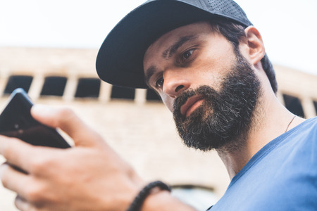 Young handsome bearded man using his smartphone on the street. Blurred background. Horizontal