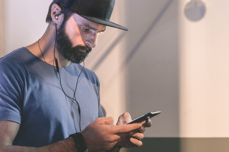 Bearded pensive man wearing black snapback cap standing on cafe with headphones. Men using mobile phone for listening digital music on smartphone.Blurred background. Horizontal. Visual effects Stock Photo