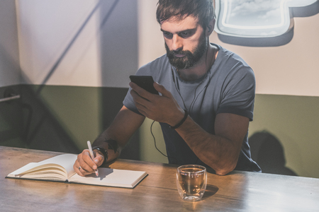 Young bearded man sitting in cafe with headphones. Men using mobile phone for listening digital music on smartphone. Man making notes at note book. Horizontal. Blurred background. Colors masks Stock Photo