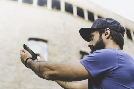 Bearded muscular man wearing black snapback cap and making selfie with his own smartphone. Man walking on street and using mobile.Blurred background. Horizontal Stock Photo - 101299082