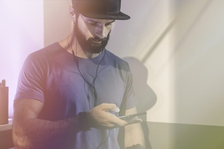 Bearded pensive man wearing black snapback cap standing on cafe with headphones. Men using mobile phone for listening digital music on smartphone.Blurred background. Horizontal. Visual effects.Flares