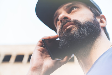 Portrait of bearded young man using his smartphone on the street. Blurred background. Horizontal. Visual effects Stock Photo - 101299087