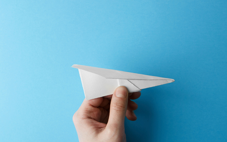 Paper plane on blue background holding in male hand. Travel and tourism concept. Horizontal