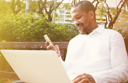 Smiling american african businessman in informal clothes working at sunny street on laptop and smartphone for calling friends via social networks