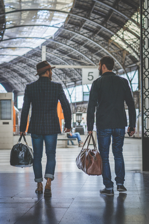 Two confident multi-ethnic bearded businessmans together wearing casual clothes and holding travel bags in hands waiting the train on the railway platform.Vertical