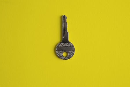 Door key in center of empty yellow background. Top view Stock Photo