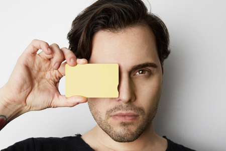 Young man holding empty yellow color credit card front of male face on blank white background. Business mock-up background for message writing. Horizontal Mockup.