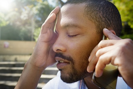 Closeup portrait of tired young African-American businessman using mobile phone outdoor
