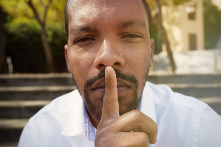 Close up portrait of handsome cheerful silent american african man making hush gesture.