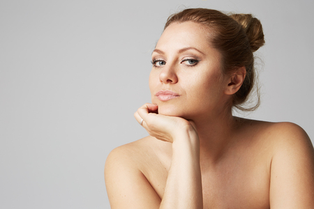 Beautiful girl with big eyes and dark eyebrows, with naked shoulders, looking at camera.Model with light nude make-up, gray studio background, beauty photo, copy space, close up