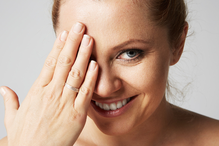 Young beautiful women with blonde hair fixed behind, big eyes, and naked shoulders smiling and closes her eyes with one hand on gray background.Closeup portrait, copy paste space Stock Photo