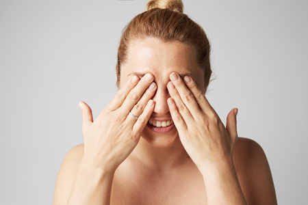 Young beautiful women with blonde hair fixed behind, big eyes, and naked shoulders smiling and closes her eyes with two hands on gray background.Closeup portrait, copy paste space