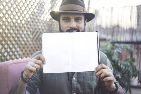 Attractive Hipster blogger holding notepad with open blank sheets on hands, while spending time on terrace of cafe.Space for Copy paste text. Film effect