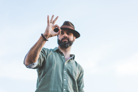Handsome happy bearded hipster looking at camera through his fingers in ok gesture. People Watching concept Stock Photo
