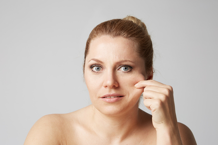 Young woman with clean skin, natural make-up, and beautiful eyes touches fingers her face on gray background. Medical and cosmetic facial skin care concept