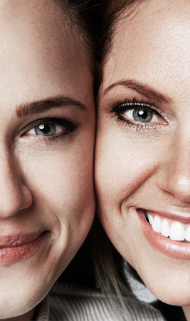 Portraits of Two Young beautiful womens with blonde and brunette hair smiling on gray studio background.Medical and cosmetic facial skin healthcare concept.Vertical