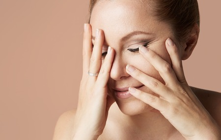 Young attractive girl with blonde hair fixed behind, closed eyes, thick eyebrows and naked shoulders holding hand near face at color background.Closeup portrait, copy paste space