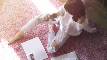 Beautiful woman sitting on pink carpet on the floor at modern light coloured living room and using electronic gadgets.Top view Stock Photo