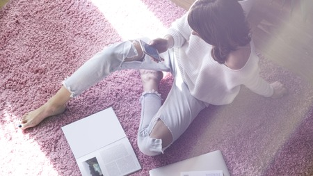 Beautiful woman sitting on pink carpet on the floor at modern light coloured living room and using electronic gadgets.Top view.Flare