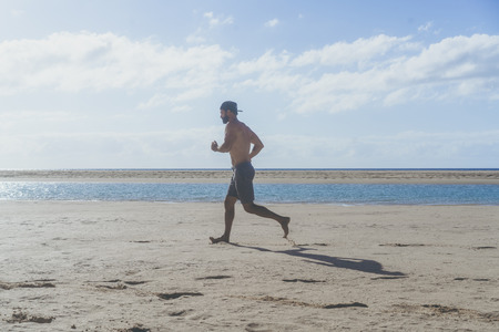 Running man jogging on beach.Muscular male runner training outside working out