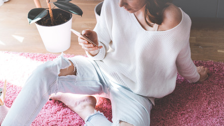 Handsome girl sitting on pink carpet on the floor at modern light coloured living room and typing hand on mobile phone Stock Photo