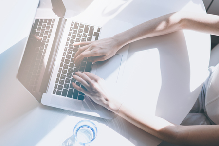 Beautiful business women typing hand on a laptop computer while sitting at the wooden table in light coloured living room of modern house.Top view.Sunny day