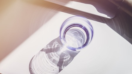 One glasses of water on sunny wooden table. Top view
