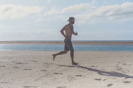 Young runner running in morning along the beach. Young bearded man jogging on the sea shore at sunrise