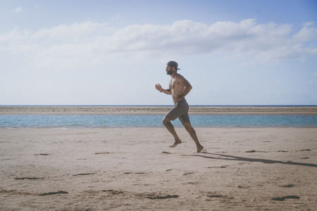 Young runner running in morning along the beach