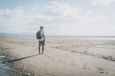 Attractive muscular bearded man standing on the sea shore at sunrise with backpack and looking horizon Stock Photo