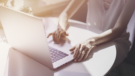 Happy casual beautiful woman working on a laptop sitting at the table in living room of modern house.Flares Stock Photo