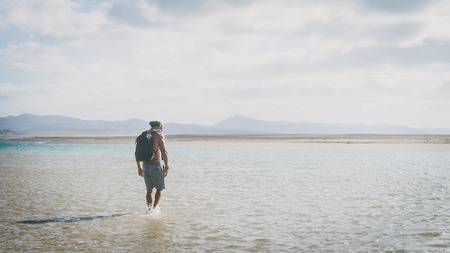 Young muscular bearded man walking on the sea shore at sunrise with backpack. Wide Stock Photo