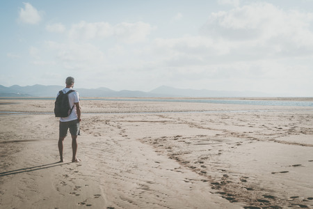 Active sport muscular bearded man standing on the sea shore at sunrise with backpack and looking horizon