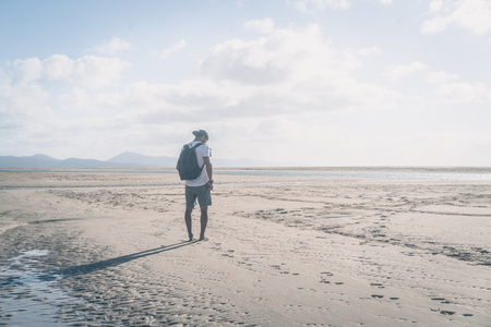 Attractive young muscular bearded man standing on the sea shore at sunrise with backpack and looking horizon