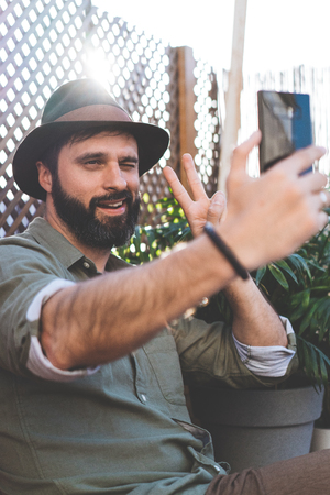 Bearded hipster making selfie via smartphone on terrace of cafe. Positive man relaxing out side
