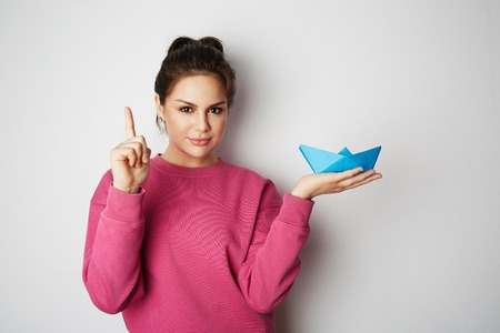 Portrait of a beautiful woman holding a blue paper ship on empty gray background.Emotions, people, beauty, fashion and lifestyle, travel, tourism and people concept. Copy paste for text