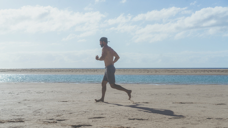 Happy bearded man jogging on the sea shore at sunrise. Side portrait of healthy young bearded man running at the beach with bright sunlight. Stock Photo