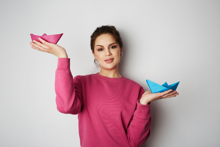 Portrait of a smiling woman holding a two blue and pink color paper ship on empty gray background.Emotions, people, beauty, fashion and lifestyle, travel, tourism and people concept. Copy paste text