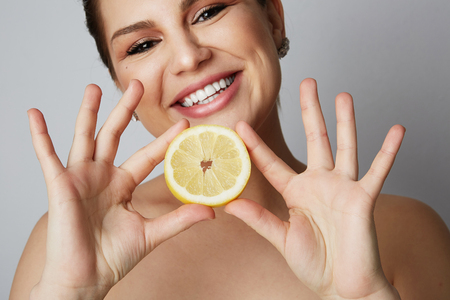 Beauty women with big blue eyes and dark eyebrows holding fresh limon and smiling at camera over gray background.Model with light nude make-up, color studio background, copy paste space, close up Stock Photo