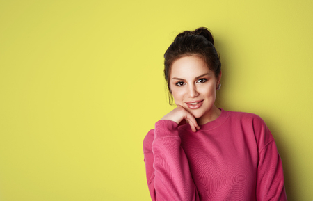 Beautiful young women with big brown eyes wearing pink hoody and looking at camera over empty yellow background.Model with light nude make-up, color studio background, copy paste text space